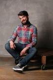 Bärtiger Mann im bunten Hemd und in den Jeans, die auf einer Plattform sitzen Stockbild