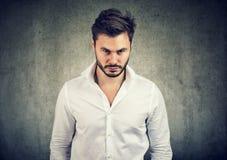Bärtiger Mann im weißen Hemd, das mit Ärger und Handlung Kamera auf grauem Hintergrund betrachtet stockfotos