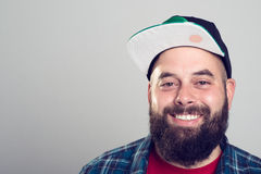 Bärtiger Mann mit Baseballmütze lächelt Stockfotos