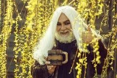 Bärtiger Mann mit Becher in der Blüte lizenzfreie stockbilder