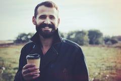 Bärtiger Mann mit der Schale Morgenkaffee gehend in Park Lizenzfreies Stockbild