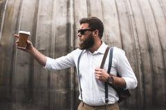 Bärtiger Mann mit der Sonnenbrille und ledernem Rucksack, die Wegwerfkaffeetasse halten und irgendwo zeigen Stockfoto