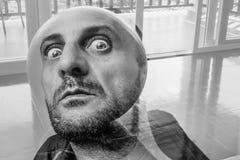 Bärtiger Mann mit drastischen großen Augen Sie, schreckliches Porträt aufpassend des gequälten Mannes mit Kopf in Form von Ballon lizenzfreies stockbild