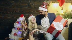 Bärtiger Mann mit einer großen Geschenkbox sitzt nahe einem schönen Mädchen, das ein Glas Champagner in ihrer Hand auf Hintergrun stock footage