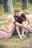 Bärtiger Mann mit Frauen im Waldhippie mit touristischer Schaufel und Frauen las Bücher Freunde, die auf Natur kampieren Leute stockfotografie