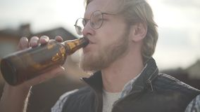 Bärtiger Mann mit Gläsern Bier trinkend und Getränk draußen genießend Kerl schmeckt Lager von der Flasche Langsame Bewegung stock footage