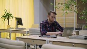 Bärtiger Mann mit Konzentration arbeitet an dem Computer, schaut oben und lächelt stock video