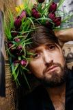Bärtiger Mann mit nettem Blumenstrauß von Blumen auf seinem Kopf Stockfotos