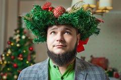 Bärtiger Mann mit Weihnachtskranz auf seinem Kopf Stockbilder