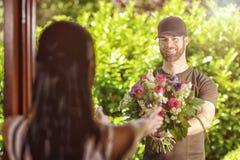 Bärtiger Mann 20s liefert Blumen an junge Frau Lizenzfreie Stockbilder