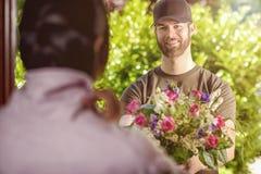 Bärtiger Mann 20s liefert Blumen an junge Frau Stockfotografie