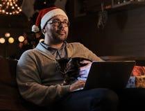 Bärtiger Mann in Sankt-` s Hut träumend auf einer Couch mit einem Laptop Lizenzfreies Stockbild