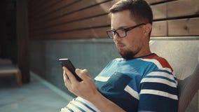 Bärtiger Mann schreibt auf dem Schirm von Smartphone und liegt auf Ruhesessel am sonnigen Tag stock video footage