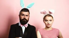 Bärtiger Mann und blonde Frau, die Augenbrauen auf einem rosa Hintergrund mit den Ohren auf ihren Köpfen hochzieht Konzept von mo stock footage