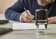 Bärtiger Mann unterzeichnet einen Vertrag stockfotografie