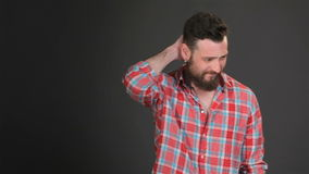 Bärtiger Mann verkratzt seinen zurück des Halses stock footage