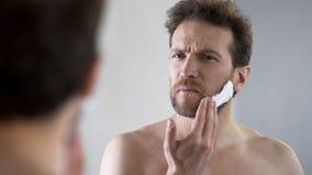 Bärtiger Mann von mittlerem Alter, der Schaum auf Gesicht, Morgenritual, Spiegel rasierend zutrifft stockbilder