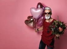 Bärtiger Mann von mittlerem Alter mit Ballonen und Blumen stockfotos