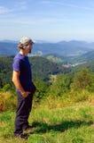 Bärtiger Mann, Wanderer, stehend in den Bergen und in den Blicken in den Abstand Rückseitige Ansicht Sonniger Tag Lizenzfreie Stockbilder