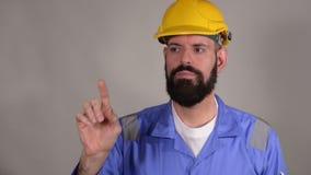 B?rtiger Mannerbauer im Sturzhelm bereit, etwas durch Finger zu schreiben stock footage