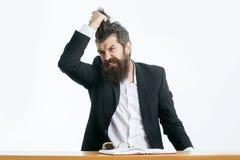 Bärtiger Mannlehrer bei Tisch Stockfotos