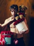 Bärtiger muskulöser Mann mit sexy Körper hält Rotrosenkasten Stockfotos