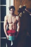 Bärtiger muskulöser Mann mit sexy Körper hält Rotrosenkasten Lizenzfreie Stockfotografie