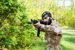 Bärtiger Soldat mit einem Gewehr im Wald Stockfotografie