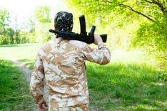 Bärtiger Soldat mit einem Gewehr im Wald Stockbild