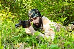 Bärtiger Soldat mit einem Gewehr im Wald Stockfoto