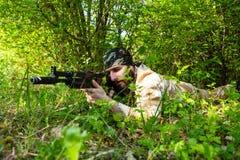 Bärtiger Soldat mit einem Gewehr im Wald Stockfotos