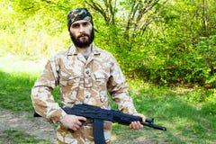 Bärtiger Soldat mit einem Gewehr im Wald Lizenzfreie Stockfotografie