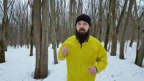 B?rtiger Sportmann, der auf Kopfh?rer und Betrieb in Wald des verschneiten Winters sich setzt stock video footage