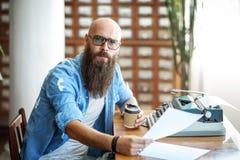 Bärtiger stilvoller Verfasser mit der Schale coffe seinen Roman lesend stockfoto