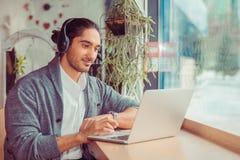 B?rtiger Student des jungen Mannes im Caf? unter Verwendung der Laptop-Computers und der h?renden Musik lizenzfreie stockbilder