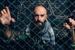 Bärtiger Terrorist in der Uniform gegen Metallgitter lizenzfreie stockfotos