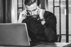 Bärtiger trauriger Geschäftsmann, der am Handy spricht lizenzfreie stockbilder