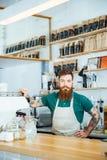 Bärtiges barista mit den tätowierten Händen in der Kaffeestube Lizenzfreie Stockbilder