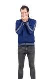 Bärtiges Bedeckungsgesicht des jungen Mannes mit seinem Handlachen stockfotografie