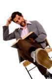 Bärtiges Buch des männlichen Kursteilnehmers Lese- Ausdrücken des Durcheinanders Lizenzfreie Stockfotografie