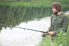 Bärtiges Fischen des junger Mann-Fischers mit Stange Lizenzfreies Stockbild
