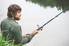 Bärtiges Fischen des junger Mann-Fischers mit Stange Stockfoto