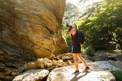 Bärtiges Fotografmanntrekking unter Wald und Bergen und nehmen Bilder mit dslr Kamera Horizontale Form Lizenzfreie Stockfotografie