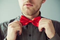 Bärtiges Gesicht und Hände, die rotes bowtie korrigieren Lizenzfreies Stockfoto