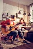 Bärtiges Gitarristgefühl zufriedengestellt, nachdem Melodie komponiert worden ist lizenzfreies stockbild