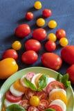 Bästa ciew av den gröna plattan med traditionell italienareCaprese sallad och spridda tomater på mörkt skifferbräde arkivfoto