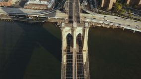 Bästa flyg- sikt av den Brooklyn bron till och med Eastet River till Manhattan i New York, Amerika Flagga som vinkar på vinden arkivfilmer