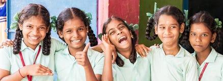 Bästa klasskompisar för barnvänflickor som ler skratta anseende med handen på skuldra på skolan Multietniska skolaungar royaltyfri foto