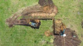 Bästa ner av bulldozern och grävskopan som gräver gropen enligt att markera på jordning arkivfilmer