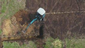 Bästa ner av grävskopan som gräver diket enligt att markera på jordning arkivfilmer